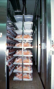 Nell'immagine una moderna cella frigorifera in cui i prosciutti vengono condotti su carrelli agganciati a binari); il freddo e il caldo sono regolati da un computer che gestisce tutte le fasi di lavorazione
